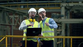 Engineers work with a laptop at a brick plant.