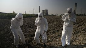 Engineers workers dressing protective hazmat clothes intoxicated with nuclear waste from near power plant falling down dying -. Engineers workers dressing stock footage