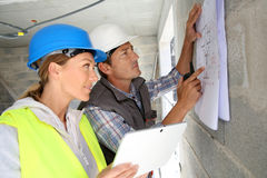 Engineers working on blueprint on building site Stock Photos