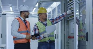 Engineers working with electrical equipment on station stock photography