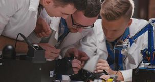 Engineers working on kinetic glove with soldering iron