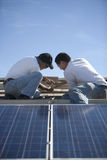 Engineers Working On Solar Panelling At Rooftop. Two engineers working on solar panelling at rooftop against blue sky Royalty Free Stock Images