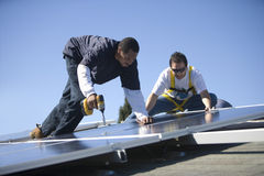 Engineers Working On Solar Panels Against Sky Royalty Free Stock Photo
