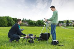 Engineers Working On UAV Helicopter in Park. Side view of young engineers working on UAV helicopter in park royalty free stock photos