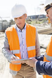Engineers writing on clipboard at construction site Royalty Free Stock Photo