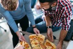 Enginneers de logiciel partageant la pizza sur la coupure du travail Photographie stock