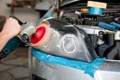 Enginner del mecánico de automóviles que pule una linterna de un coche moderno Foto de archivo