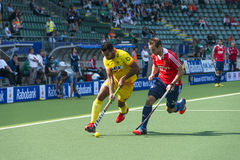 England Beats India at the World Cup Hockey 2014. THE HAGUE, NETHERLANDS - JUNE 2: Englishman Catlin reaches for the ball to stop a rush by Indian player royalty free stock image
