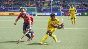 England Beats India at the World Cup Hockey 2014. THE HAGUE, NETHERLANDS - JUNE 2: Englishman Catlin reaches for the ball to stop a rush by Indian player stock image