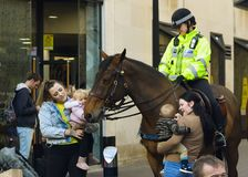 Members of Public and Friendly Mounted Police Officer. England, Bristol - Oct 30, 2017: Members of Public and Friendly Mounted Police Officer, Small Babies Stock Photo