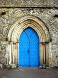 England: Cartmel Priory church blue door stock photo