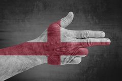England flag painted on male hand like a gun. On concrete background stock photos