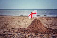 A England flag on a sand castle on a British Beach. An England St George`s cross flag on a United Kingdom beach representing patriotism during the itical Brexit royalty free stock images
