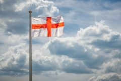 England Flag in the sky. National England Flag of Saint George in the wind on a flagpole against a background of clouds in the sky stock image