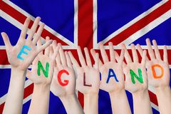 England inscription on the children`s hands against the background of a waving flag of the Great Britain.  royalty free stock image