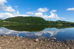 England lake District Ullswater blue sky on beautiful still summer day with reflections from sunny weather. England lake District Ullswater with mountains and stock photo