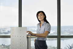 England, London, Canary Wharf, businesswoman standing behind lectern, giving presentation Royalty Free Stock Photography