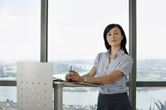 England, London, Canary Wharf, businesswoman standing behind lectern, giving presentation Stock Photography