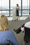 England, London, Canary Wharf, businesswoman standing behind lectern, giving presentation Royalty Free Stock Photos