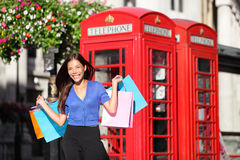 England London shopping woman shopper with bags. England London shopping woman shopper holding shopping bags by red phone booth. Female shopper smiling in London Stock Photography