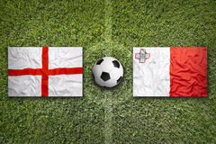 England and Malta flags on soccer field Stock Images