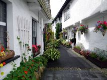 England: old lane with white cottages. Old narrow lane with white stone cottages and flower planters in Hawkshead, the Lake District, Cumbria Stock Images