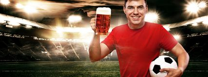 England or Russian football sports fun - happy man at oktoberfest, taking beer and soccer ball on stadium. Stock Photos