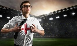 England soccer or football supporter showing flag. Under his business shirt on stadium stock image