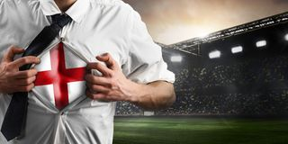 England soccer or football supporter showing flag. Under his business shirt on stadium royalty free stock photography