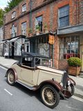 England: vintage car and old shops. Classic vintage car parked outside row of old shops in England royalty free stock image