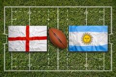 England vs Argentina flaggor på rugbyfält royaltyfri foto