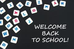 Englisch färbte quadratische Buchstaben zerstreut auf schwarzen Hintergrund mit Textwillkommen zurück zu Schule stockfoto