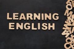 Englisch lernend, buchstabierte mit hölzernen Buchstaben auf schwarzem Hintergrund stockbilder