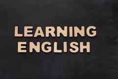 Englisch lernend, buchstabierte mit hölzernen Buchstaben auf schwarzem Hintergrund stockfotos
