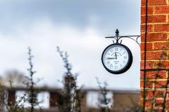 Englische Backsteinhausecke mit dem Baumeln der Retro- Uhr mit Paddington-Stations-London-Text auf ihm stockfoto