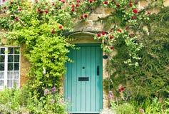 Englische Häuschengrüntüren und rote Rosen Stockfoto
