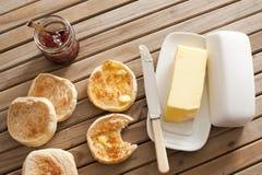 Englische Muffins, Butter und Stau auf Holztisch Stockfoto