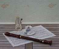 Englische Teetasse und Untertasse mit Blumendekor und silberne Kante, Taktmesser für Musik und eine Blockflöte auf einem Notenbla lizenzfreie stockfotografie