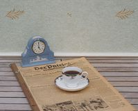 Englische Teetasse und Untertasse vor einer hellblauen Wedgwood-Uhr, Jasperware, auf einem alten deutschen Tageszeitung Der-Patri lizenzfreie stockfotos