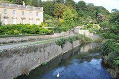 Englische Villa durch einen Fluss Stockbilder
