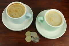Englische Währung mit zwei Kaffeetassen Stockfotos