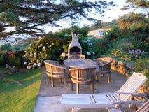 Englischer Garten mit hölzernen Gartenluxusmöbeln Lizenzfreies Stockbild