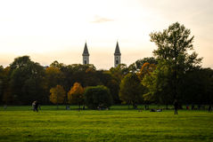 Englischer Garten Munich. The towers of a church rise in the background while strollers walk in the park Stock Images