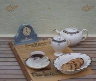 Englischer Teesatz vor einer hellblauen Wedgwood-Uhr, Jasperware, auf einem alten deutschen Tageszeitung Der-Patrioten stockbild