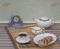 Englischer Teesatz vor einer hellblauen Wedgwood-Uhr, Jasperware, auf einem alten deutschen Tageszeitung Der-Patrioten lizenzfreie stockfotos