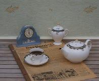 Englischer Teesatz vor einer hellblauen Wedgwood-Uhr, Jasperware, auf einem alten deutschen Tageszeitung Der-Patrioten stockfotografie