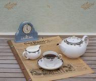 Englischer Teesatz vor einer hellblauen Wedgwood-Uhr, Jasperware auf einem alten deutschen Tageszeitung Der-Patrioten lizenzfreies stockfoto