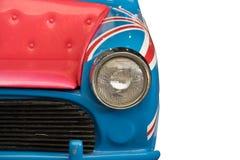 Englisches Auto, Scheinwerfer, Haube ändern als rosa Sofa auf lokalisiertem weißem Hintergrund stockfoto