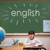 English against cute pupil sitting at desk stock photo
