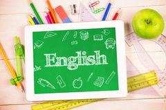 English against students desk with tablet pc. The word english and education doodles against students desk with tablet pc Royalty Free Stock Photos